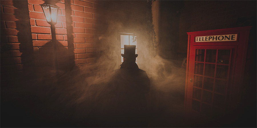 English phone booth situated in a foggy dark alley and man standing in the fog